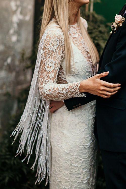 Bride and groom embrace at city celebration with botanical styling wearing a lace boho style dress
