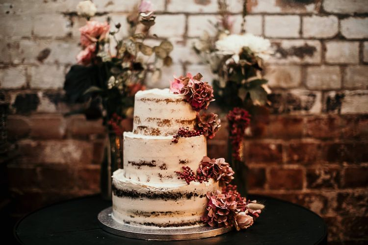 Semi naked cake with pink floral decoration for city industrial styled celebration