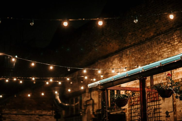 Outdoor reception decor with foliage details and festoon lighting for a city celebration