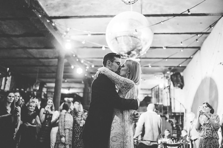 Bride and grooms first dance with festoon lighting and disco ball decor