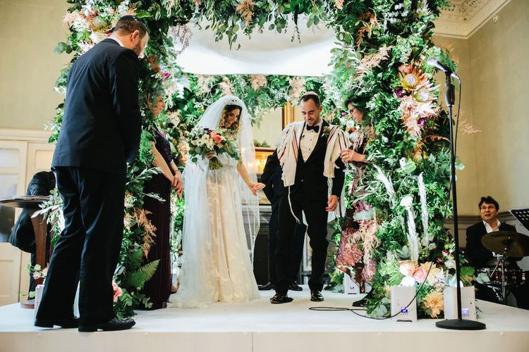 Jewish Wedding Breaking The Glass Under Floral Arch by Daisy Ellen Floral Design Image by The Crawleys