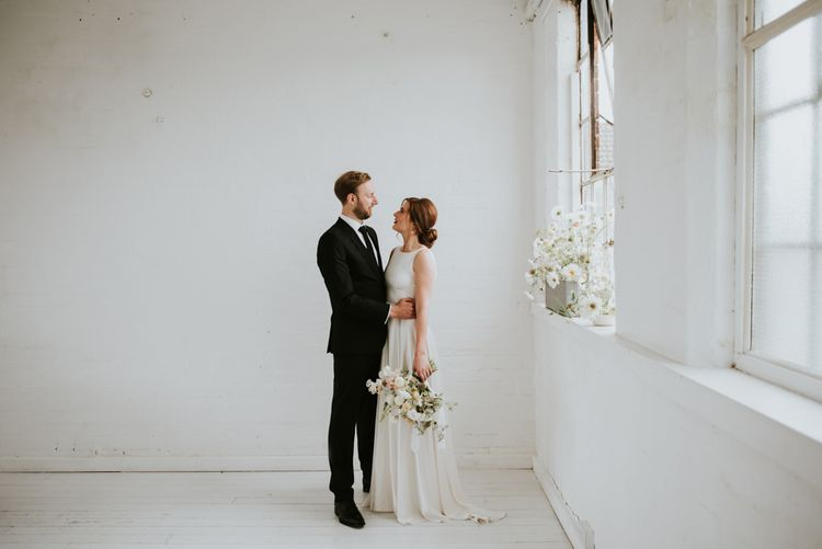 Bride in KATYA KATYA wedding dress and groom in black suit for minimalist wedding