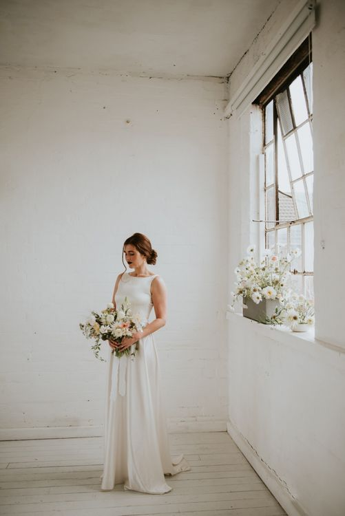 Bride in minimalist wedding dress holding a yellow and white flower bouquet