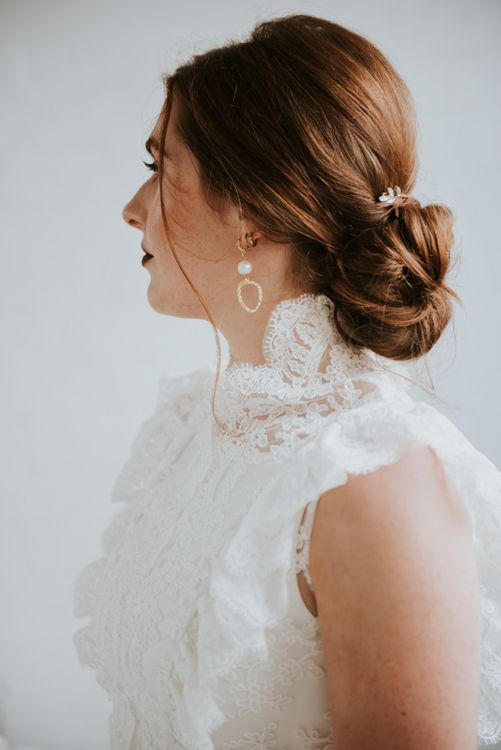 Stylish bride in sleeveless wedding dress with pinned up do