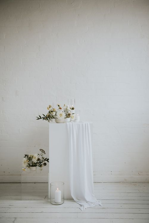 Minimalist wedding decor and flowers on acrylic plinths
