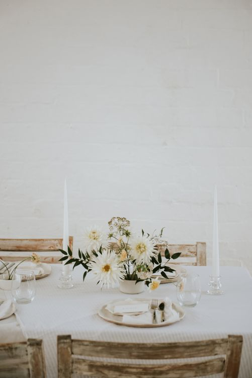 Minimalism table decor with white candles and flower centrepiece