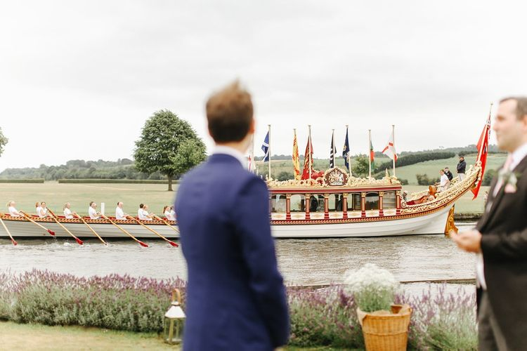 Groom in Navy Blue TM Lewin Suit | Boat | Copper, Marble & Foliage Glass Marquee Wedding & Outdoor Ceremony on Temple Island in Oxfordshire | Belle and Beau Fine Art Photography
