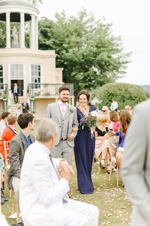 Wedding Ceremony | Wedding Party Entrance | Groomsmen in Light Grey French Connection Suit | Bridesmaid in Navy Blue Gown | Copper, Marble & Foliage Glass Marquee Wedding & Outdoor Ceremony on Temple Island in Oxfordshire | Belle and Beau Fine Art Photography