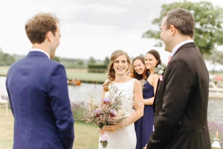 Wedding Ceremony | Bride in Alan Hannah Gown | Groom in Navy Blue TM Lewin Suit | Copper, Marble & Foliage Glass Marquee Wedding & Outdoor Ceremony on Temple Island in Oxfordshire | Belle and Beau Fine Art Photography