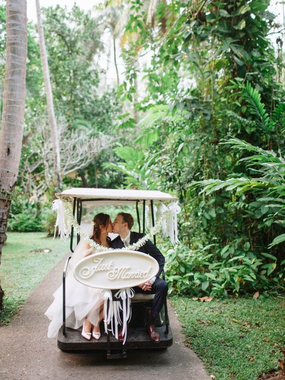 Bride and groom on a gold buggy at a Tropical wedding