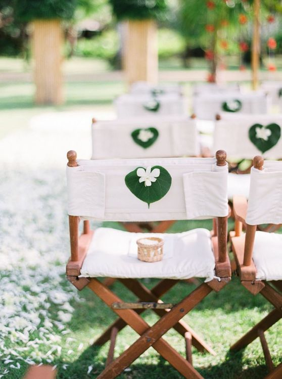 White director chairs with tropical wedding flowers on the back