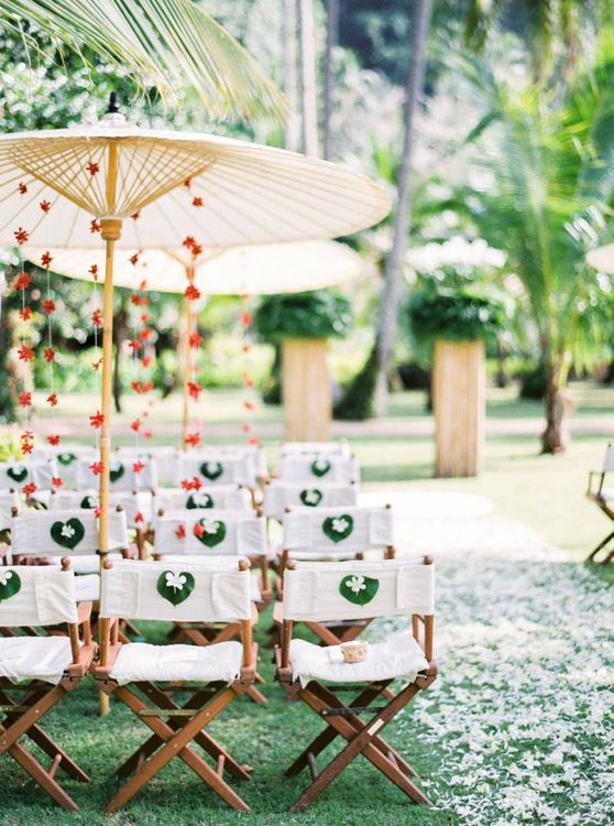 Outdoor tropical wedding decor with director chairs and parasols