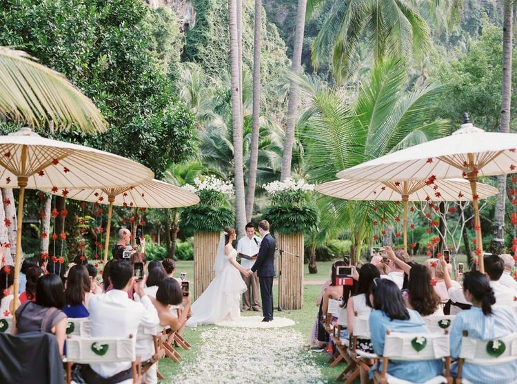 Bride and groom exchanging vows at Thailand tropical wedding