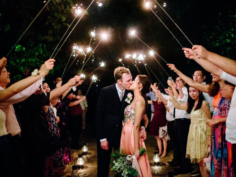 Sparkler moment at tropical wedding with bride in pink second wedding dress