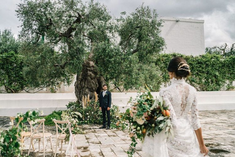 Groom in Navy Suit Waiting for His Bride at the Altar with Floral Arrangements