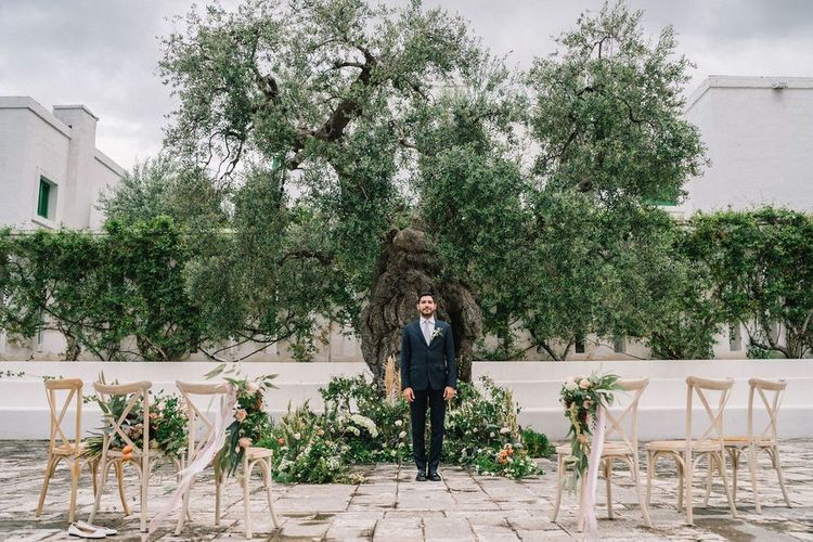 Groom in Navy Suit at the Altar Surrounded by Foliage and Flower Floral Arrangements