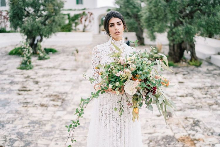 Bride in Lace Andrea Sedici Wedding Dress Holding an Oversized Romantic Wedding Bouquet