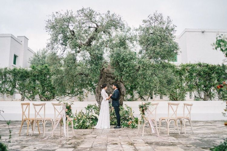 Bride in Lace Wedding Dress and Groom in Navy Suit Standing at the Outdoor Ceremony Altar