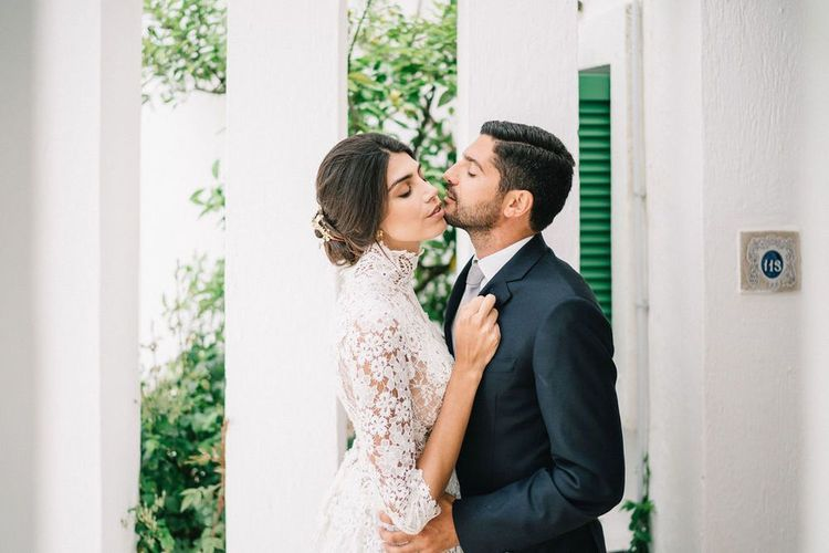 Bride in Lace Wedding Dress and Groom in Navy Suit Embracing