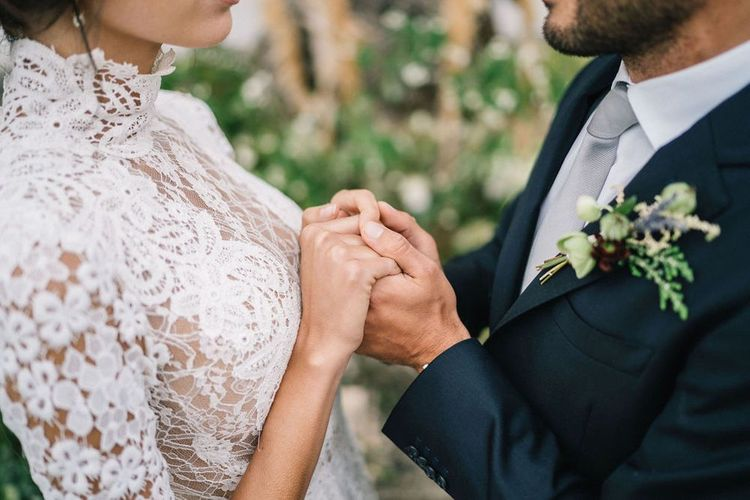 Bride in Lace Wedding Dress and Groom in Navy Suit Holding Hands