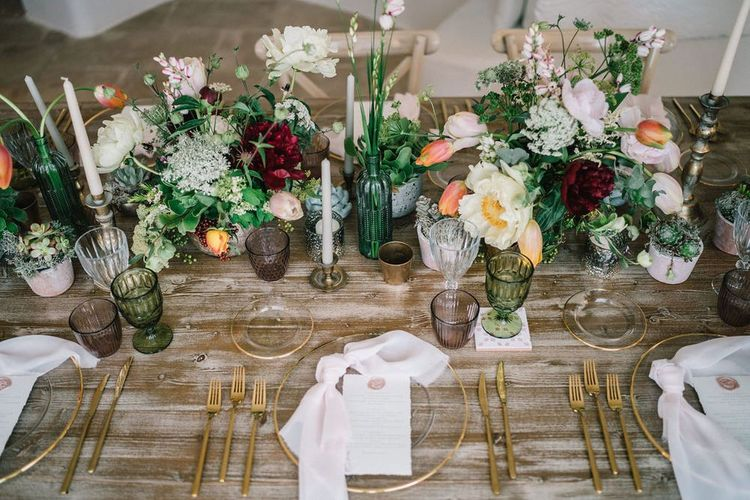 Elegant Tablescape with Gold Charger Plate and Cutlery and Lots of Flowers in Vases