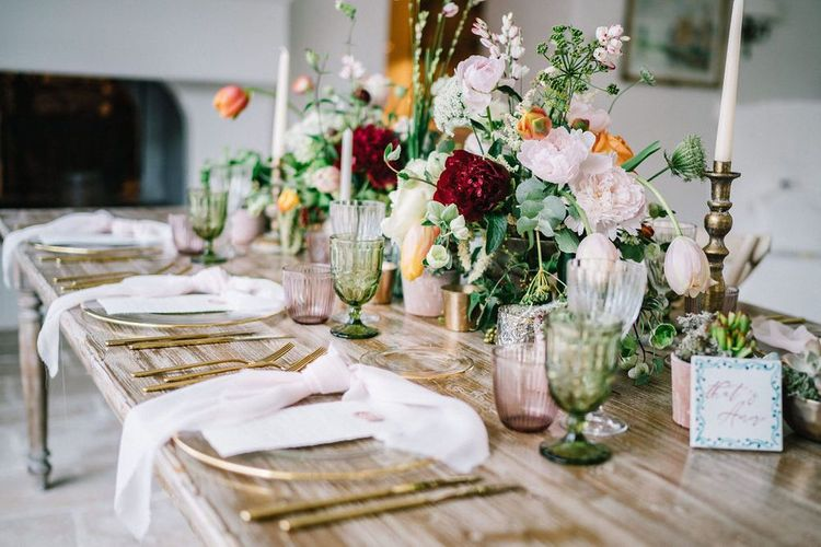 Wedding Reception Table Decor with Glass Charger Plate, Gold Cutlery, Candlesticks and Floral Centrepieces