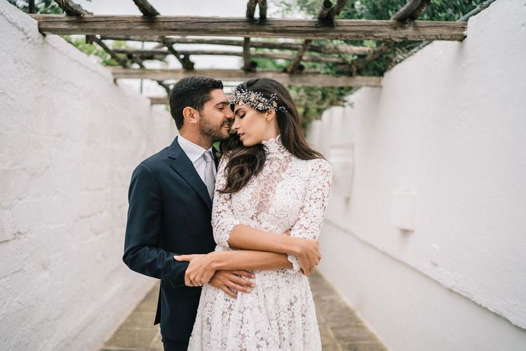 Bride in Lace Wedding Dress and Hair Accessory and Groom in Dark Suit