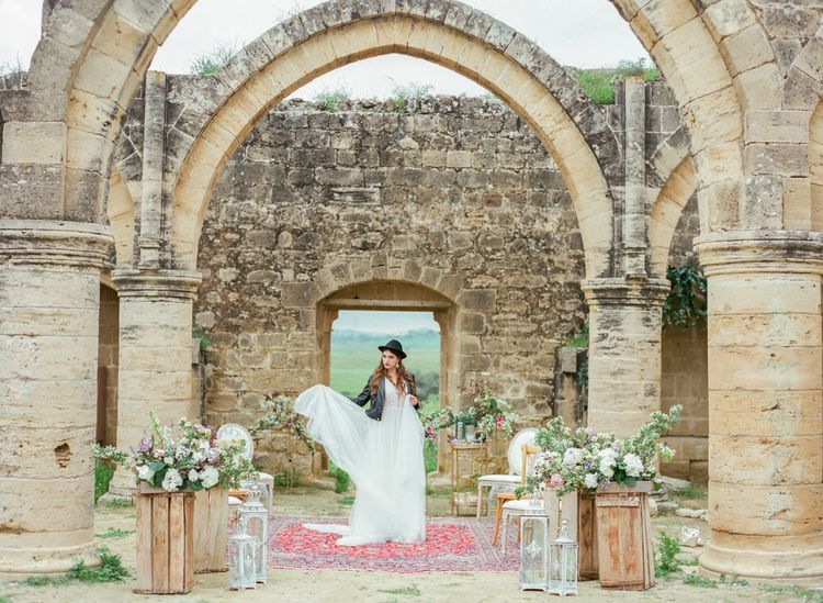 Bride in Black Leather Jacket and Fedora Standing on Persian Rugs at  Agios Sozomenos Ancient Church