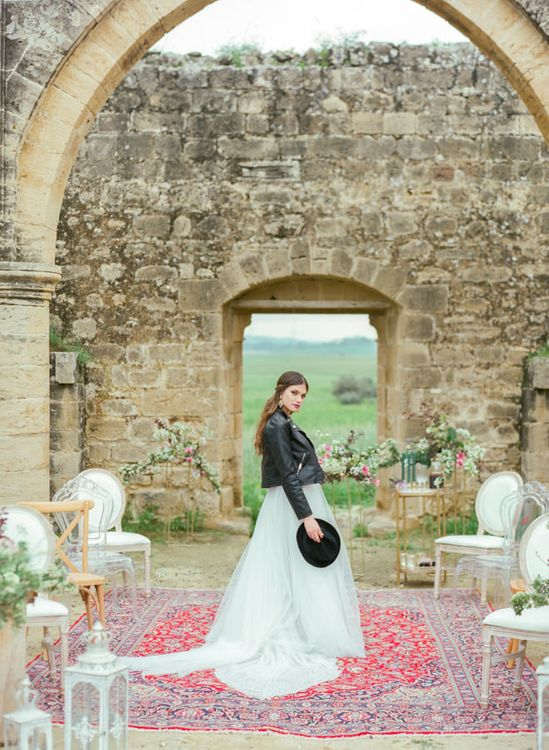 Bride in Sparkly Wedding Dress, Black Leather Jacket and Fedora Hat Standing on a Persian Rug