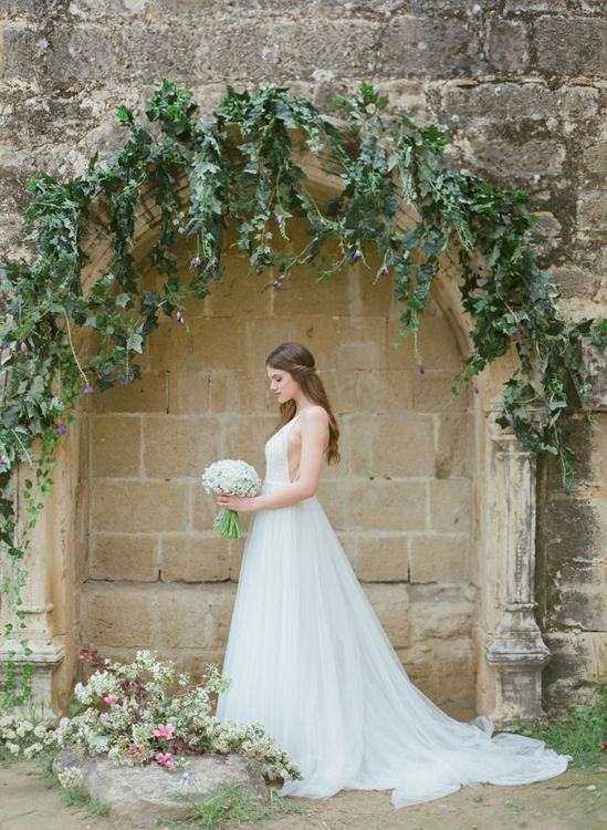 Bride in Sparkly Wedding Dress Holding a Posey of White Flowers