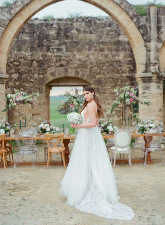 Bride in Tulle Wedding Dress Standing at Agios Sozomenos Church Ruins in Cyprus with Beautiful Romantic Tablescape