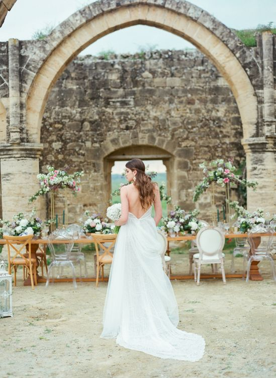 Bride in Low Back Dress Standing at Agios Sozomenos Church Ruins in Cyprus with Beautiful Romantic Tablescape