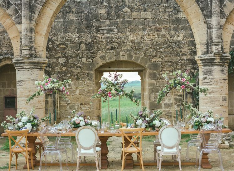 Romantic Tablescape at Agios Sozomenos Church Ruins in Cyprus with Ghost Chairs and Tall Floral Arrangements