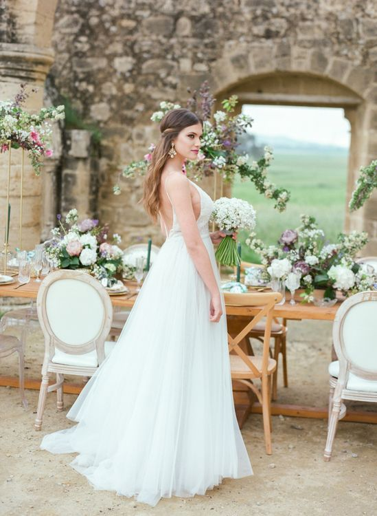 Bride in Sparkly Gala Montenapoleone Wedding Dress Standing in Front of a Romantic Tablescape at Agios Sozomenos Church Ruins in Cyprus