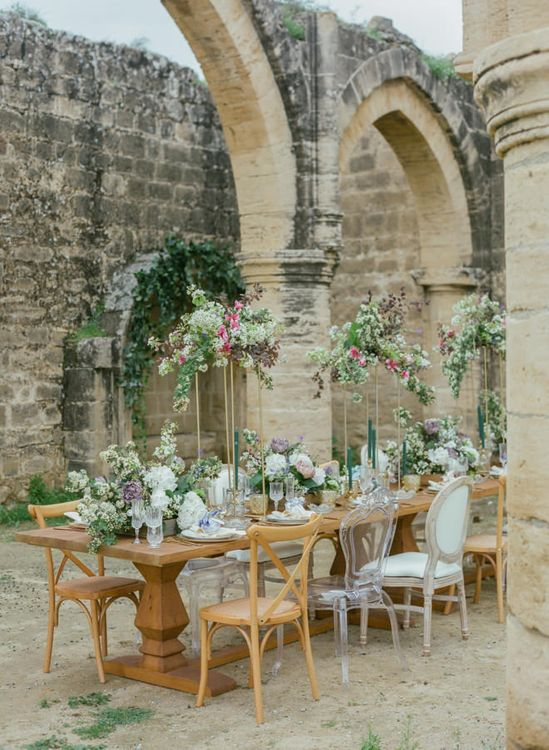 Romantic Tablescape at Agios Sozomenos Church Ruins in Cyprus with Tall Copper Frame Centrepieces, Low Wooden Crate Centrepieces and Ghost Chairs
