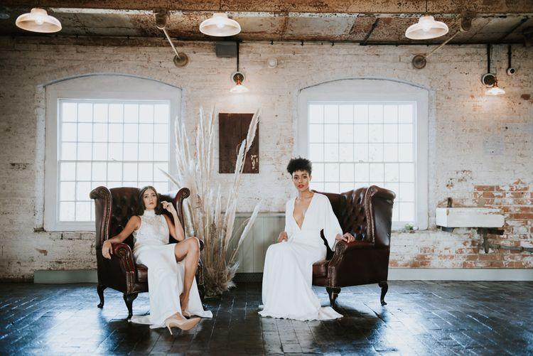 Brides sitting on leather chairs at The West Mill with pampas grass floral arrangement