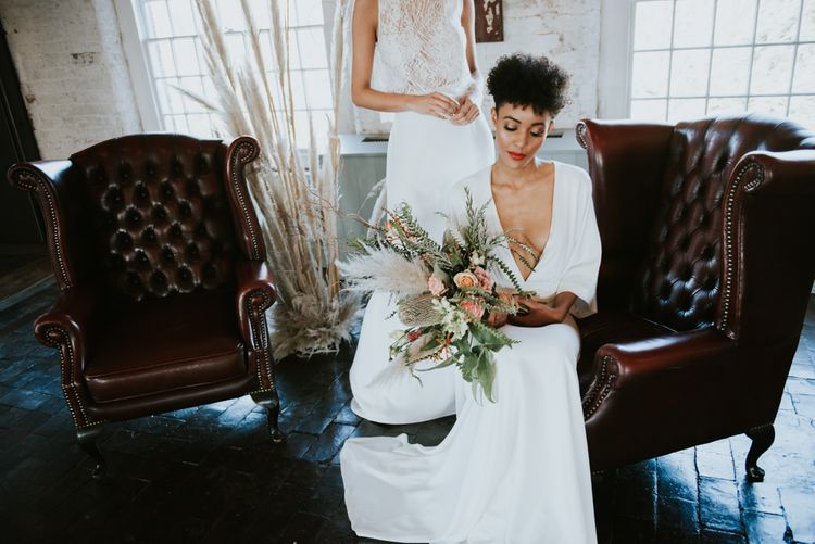 Bride with short curly hair holding a wedding bouquet