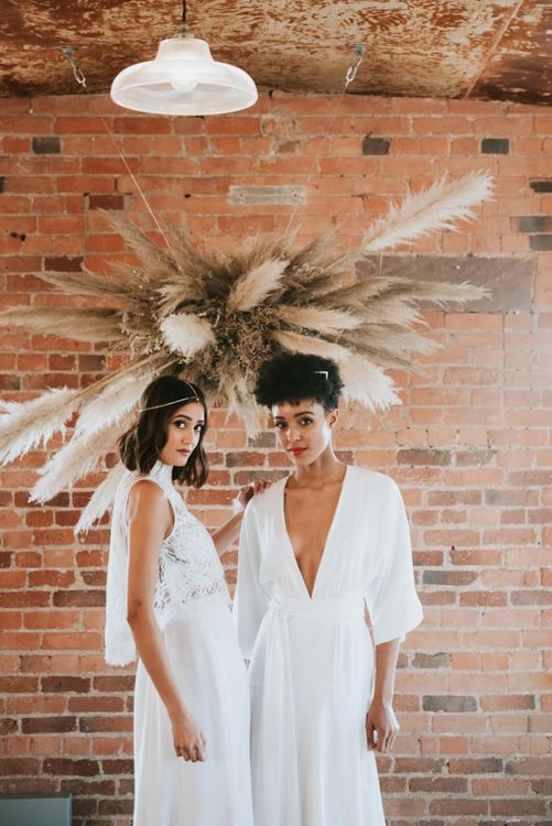 Two brides standing by a pampas grass installation at The West Mill
