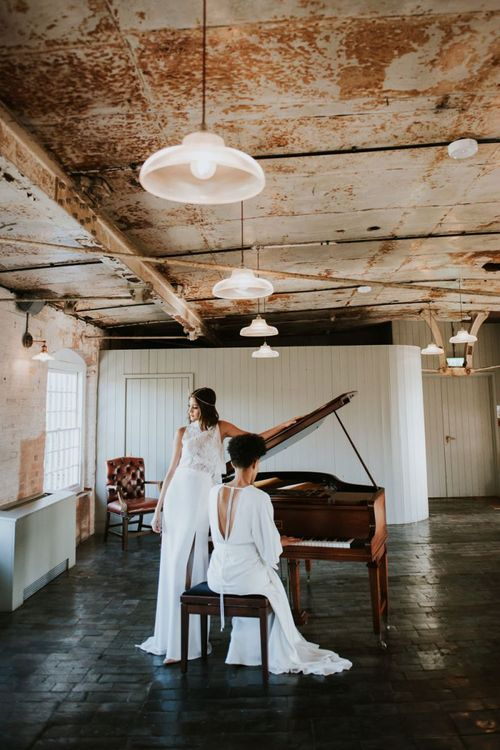 Two brides sitting at the piano at The West Mill industrial wedding venue
