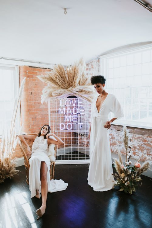 Two brides standing next to the neon wedding sign