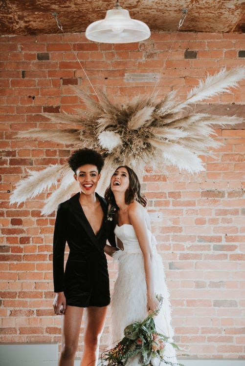Brides in short black dress and feather skirt at The West Mill wedding venue