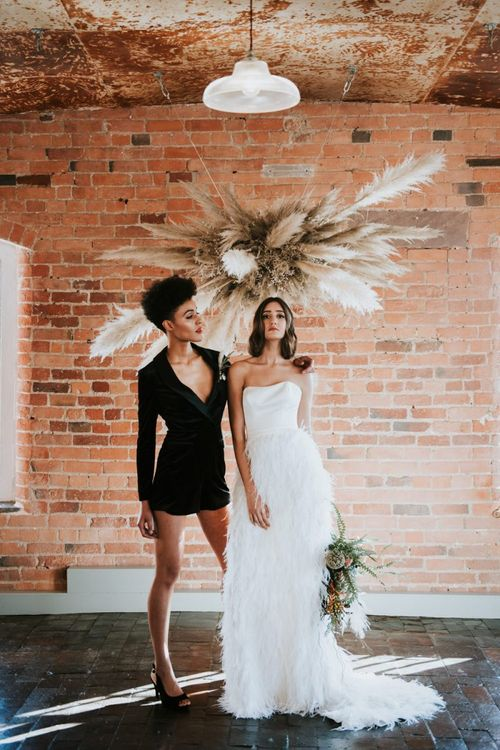 Brides in short black dress and feather skirt at  Industrial wedding venue