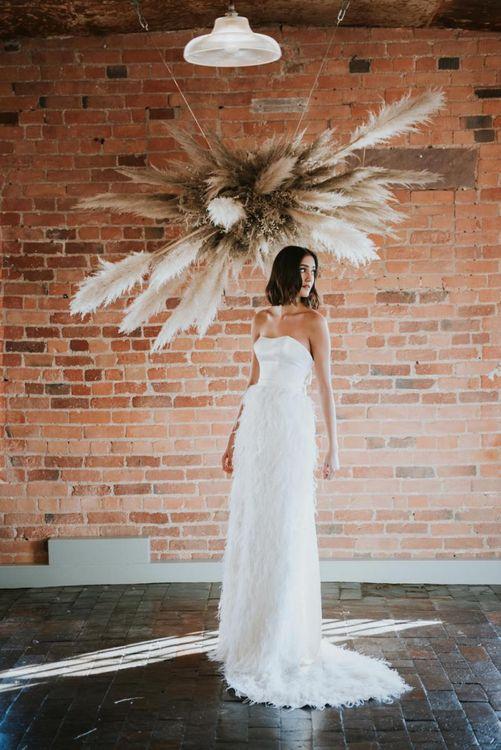 Bride in feather skirt standing under a pampas grass installation