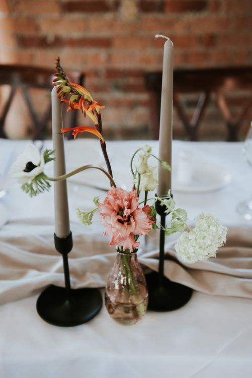 Coloured taper candle and flower stem in a vase