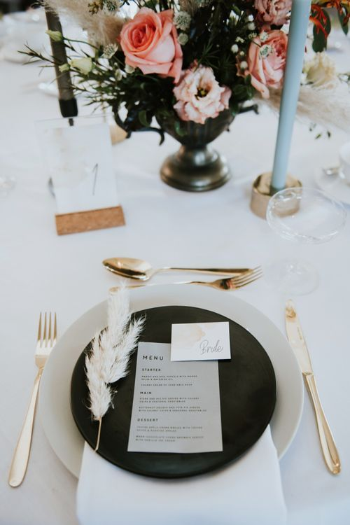Place setting with black tableware, gold cutlery and pampas grass