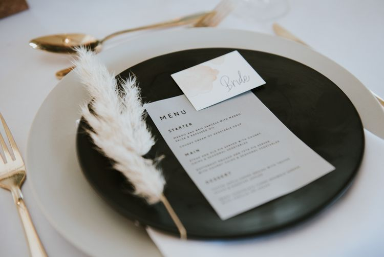 Place setting with menu and name place card decorated with a pampas grass leaf