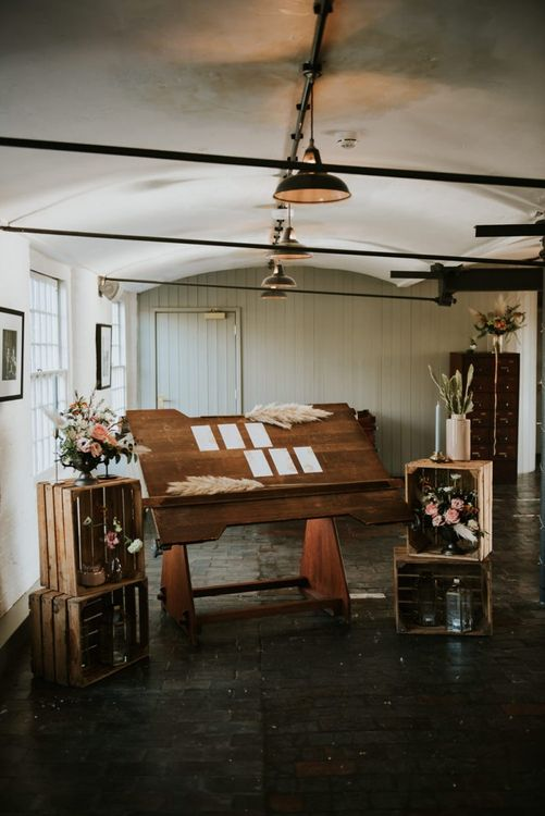 Table plan on wood stand with wooden crates  and floral decor at The West Mill