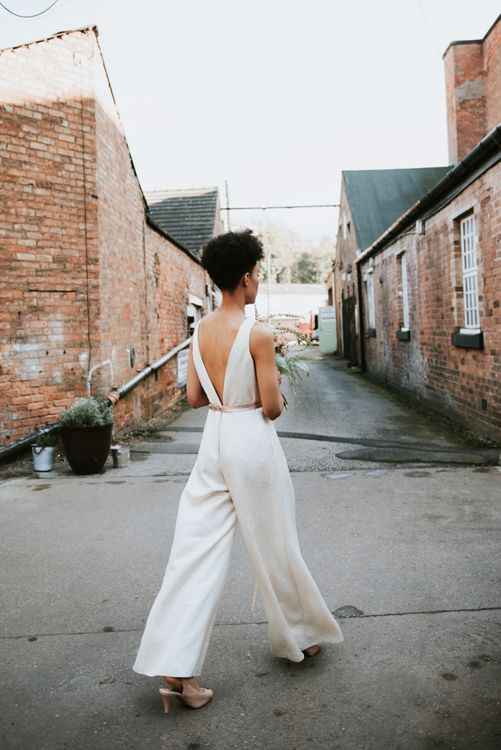 Bride with short curly hair in bridal jumpsuit at The West Mill wedding venue