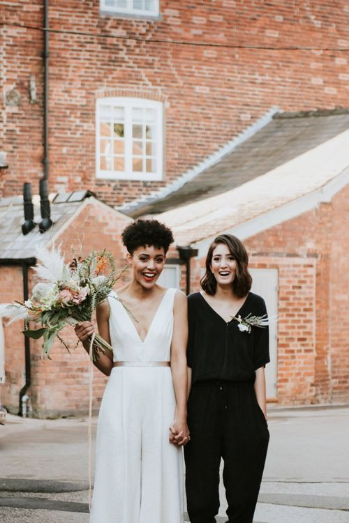 Two brides in black and white wedding jumpsuits at The West Mill wedding venue
