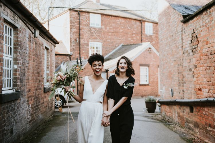 Two brides holding hands at The West Mill wedding venue